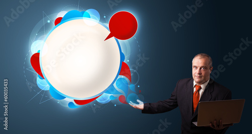 Businessman holding a laptop and presenting abstract modern spee