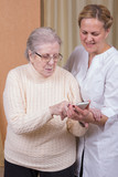 Nurse helping elderly woman with cellphone