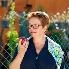 Healthy senior woman eating a red apple.