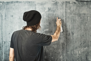 Graffiti artist spraying the wall