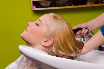 Hairdresser washing blond haired woman in the barber