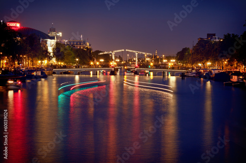 Colorful Reflection of Magere Brug Bridge in Amsterdam at Night