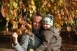 Frau mit Kind unter buntem Herbstbaum