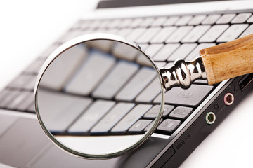laptop computer keyboard and magnifying glass