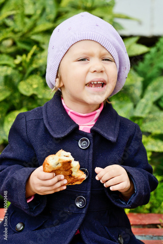 funny toddler girl eating outdoors