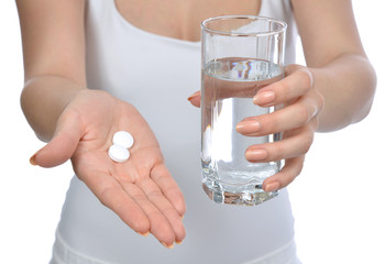 hand with pills medicine tablets and glass of water for headache