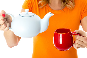 Model Released. Attractive Young Woman Pouring Tea from a Teapot