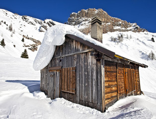 Mountain wooden cabin log in the Dolomites, Passo Fedaia