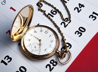 Gold pocket watch and a wall calendar