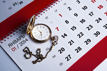 Gold pocket watch and a wall calendar