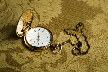 Gold pocket watch on gold cloth