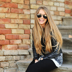 Beautiful young blond hair woman sitting on stairs and smiling w
