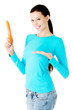 Young beautiful woman holding fresh carrot.