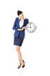 Young business woman holding clock.