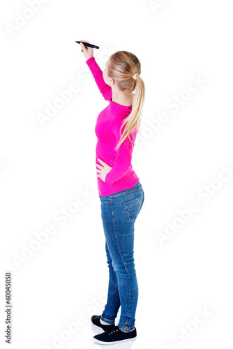 Young casual woman writing on copy space.