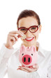 Beautiful business woman with coin and piggy- bank.