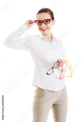 Beautiful woman in eyeglasses holding three different pair of ey