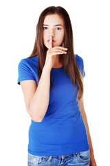 Young casual woman with finger on lips.