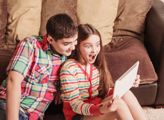 teenagers using electronic tablet at home