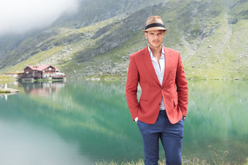 handsome young man standing near a lake