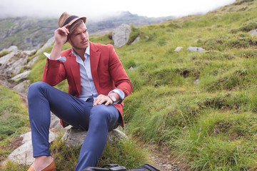 man wearing hat is sitting on rock and looking away