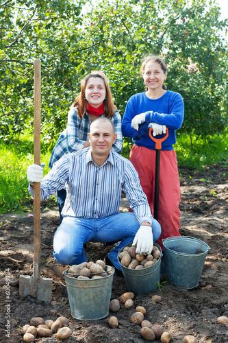 family with harvested potatoes