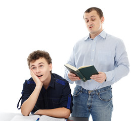 Teenager sitting at his desk showing boredom while his father is