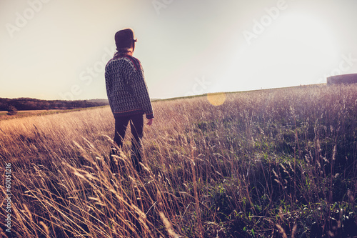 Young woman looking at sunset in meadow