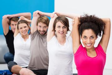 gruppe im fitnesscenter dehnt die arme