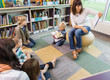 Teacher Reading Book To Children In Library - 60052886