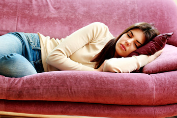 Young beautiful woman sleeping on the sofa at home