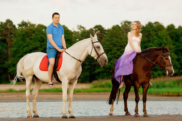 man and woman with a horses at the sea. Romantic love.