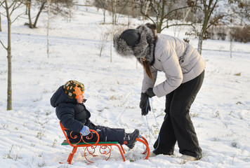 Mother and son tobogganing in the snow