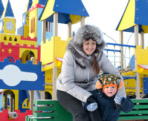 Happy mother and son in a winter playground
