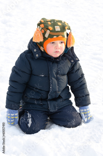 Cute small boy kneeling in winter snow