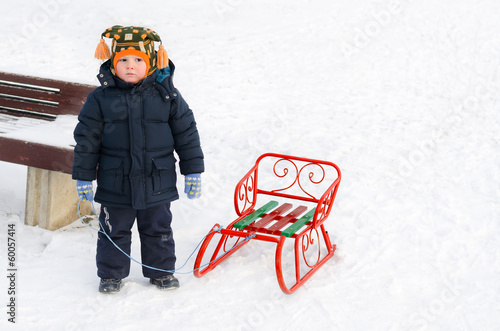 Little boy in the snow with his toboggan