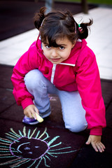 little girl painting with chalk