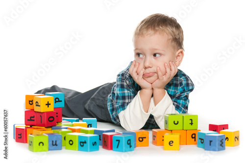 Pensive preschool boy with blocks