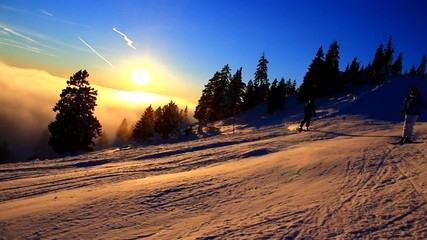 Skiiers in the sunset on the mountains.