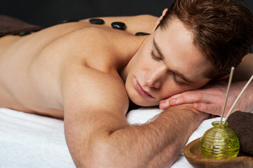 Man relaxing on a massage bed with hot stones