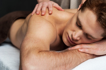 Relaxed man getting his back massaged