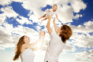 Happy family throws up baby boy against blue sky
