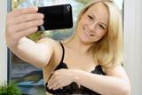 Frau nimmt Selfie mit Smartphone auf poster