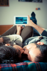 couple in love on the bed using tablet