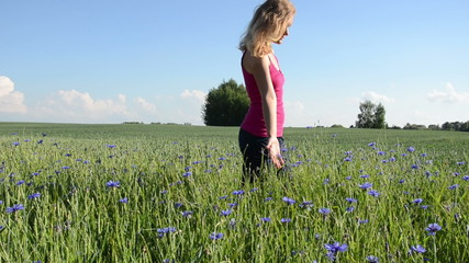woman goes enjoying the beauty flower field centaurea cyanus