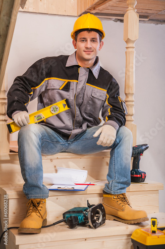 young contractor sitting on wooden ladder holding constructionh