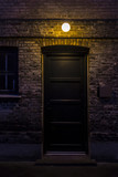 Black door in dark alley at night