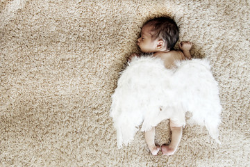 Little naked newborn baby sleeping with angel wings