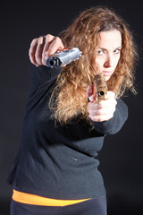 Curly sexy woman killer with handguns