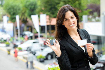 Saleswoman with car keys in trade fair